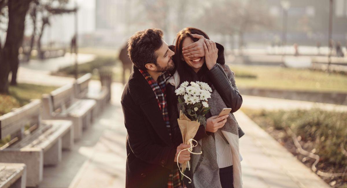Zaskoczony mężczyzna kobieta z kwiatów na Walentynki
